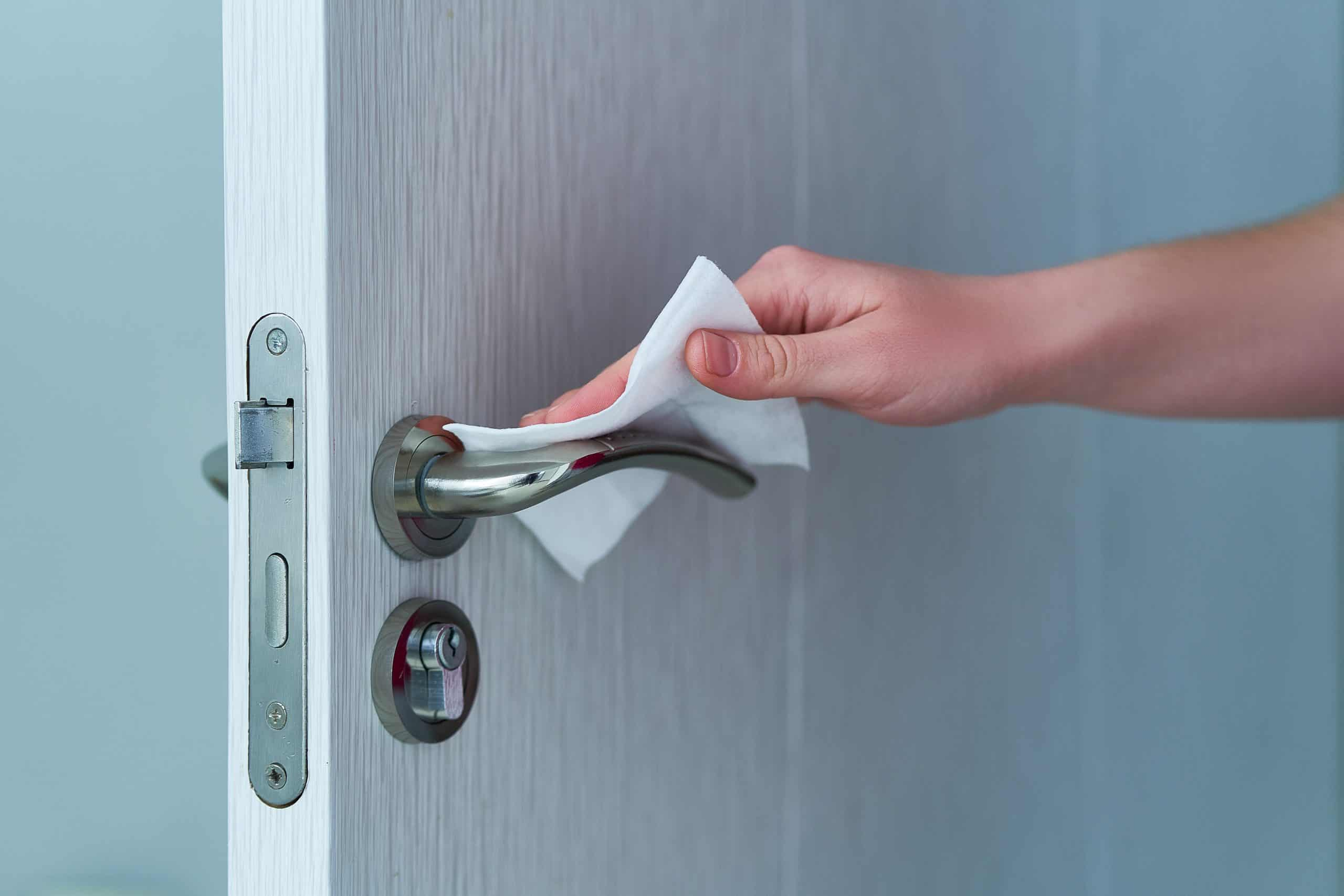 wiping a door handle with a disinfecting wipe