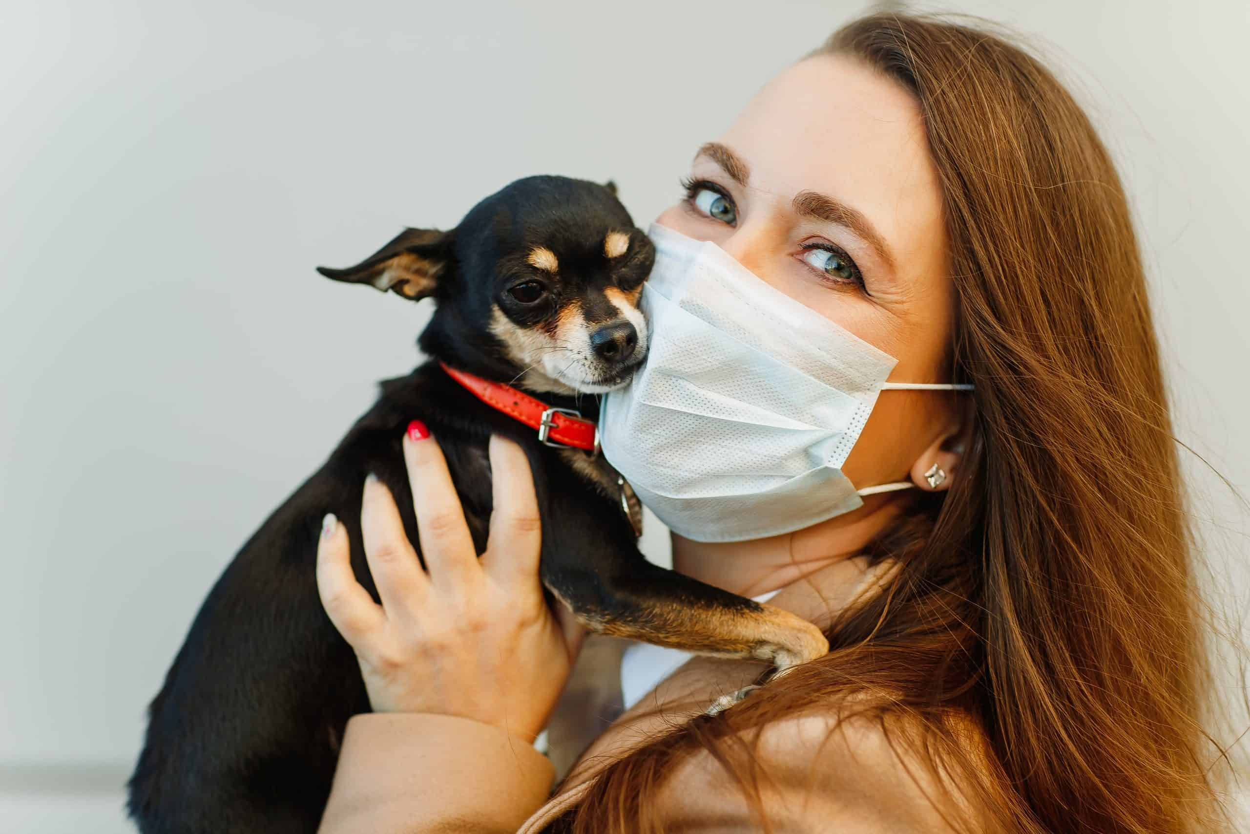 woman in face mask hugging dog close to her face